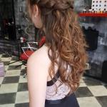 Frau mit langen brünetten Locken. Frisur einer Frau mit Flechtfrisur und langen brünetten Locken