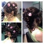 Frau mit Hochsteckfrisur. Hochsteckfrisur einer brünetten Frau mit Locken und Blüten im Haar