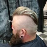 Männerhaarschnitt. Mann seitlich rasiert, oben längere Haare